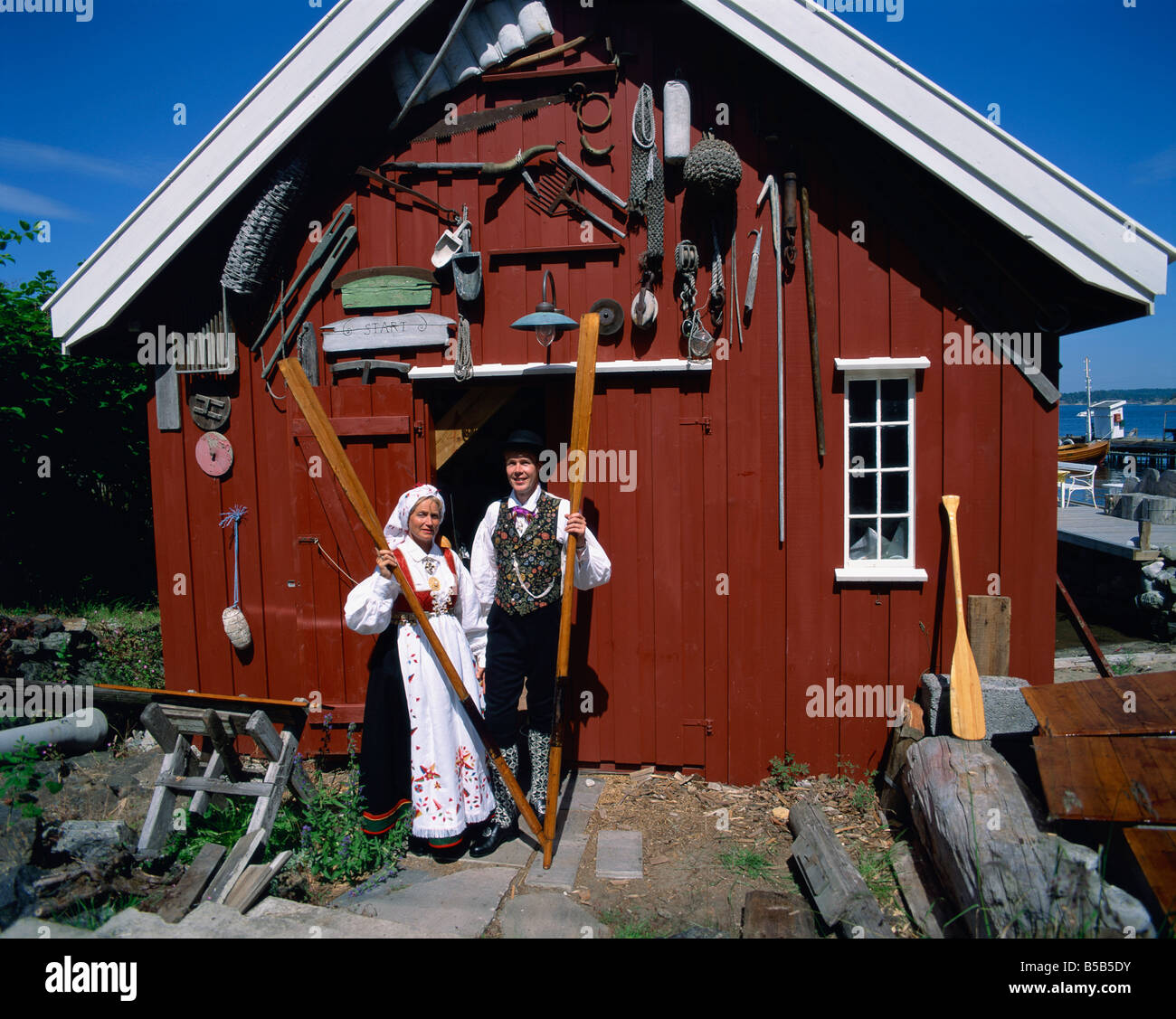 Portrait of couple in the national costume in front of wooden barn Arendal Norway A Tovy Stock Photo