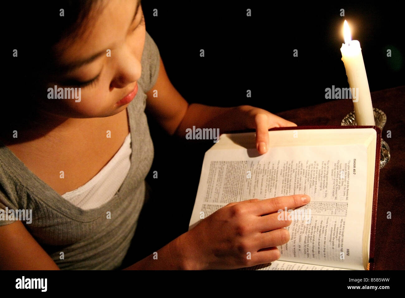 Girl reading the Bible by candlelight - Stock Image
