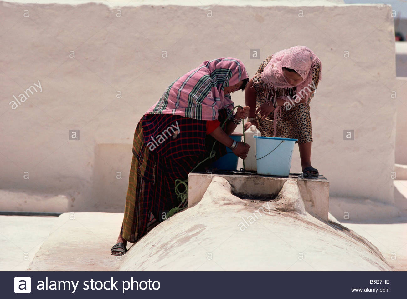 Women at mosque well, El May, Djerba, Tunisia, North Africa, Africa - Stock Image