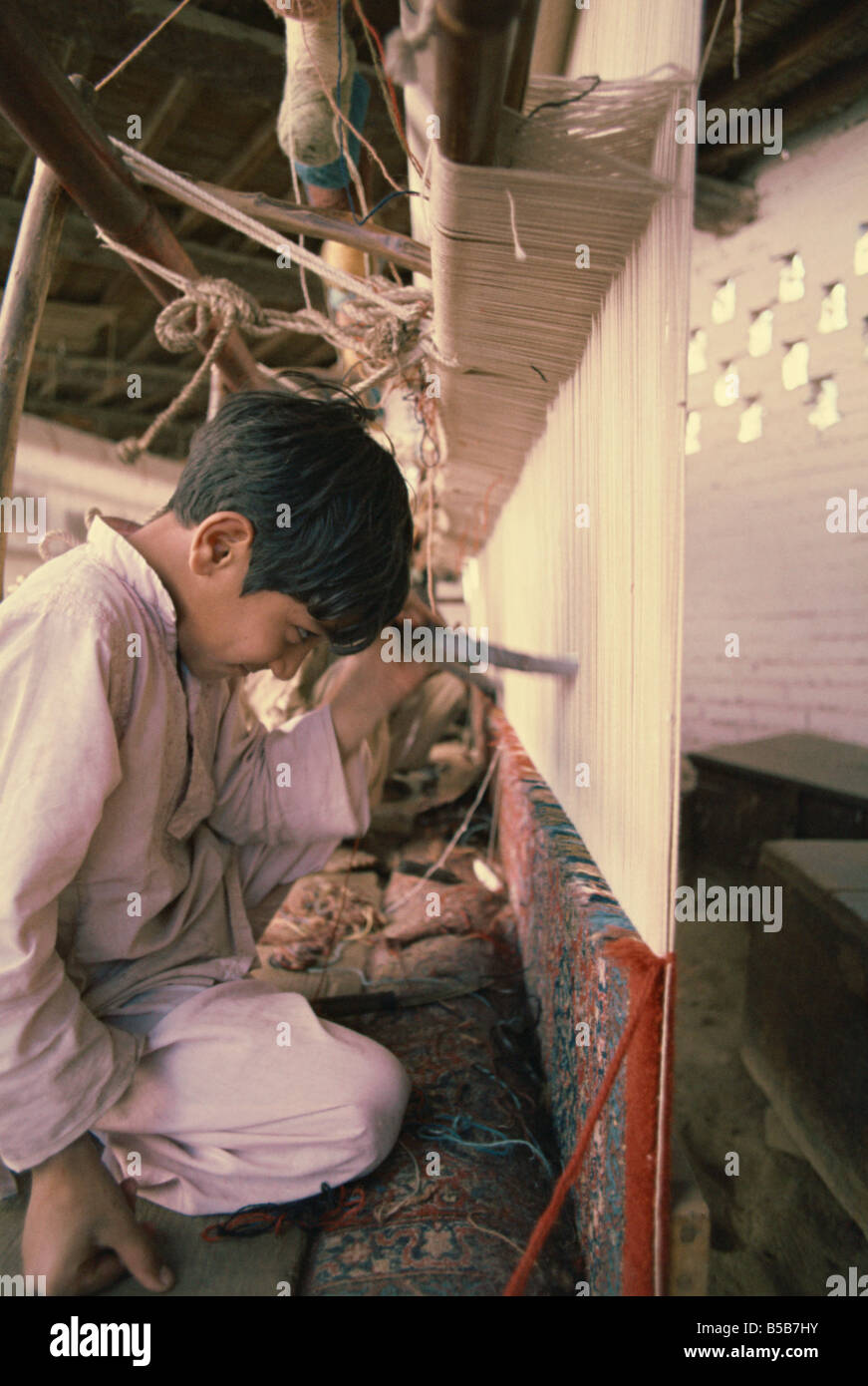 Child working in carpet factory in the 1970s Lahore Pakistan Asia - Stock Image