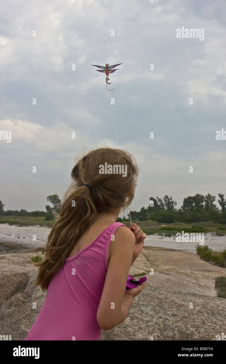 A girl flying a kite on a windy summer day - Stock Image