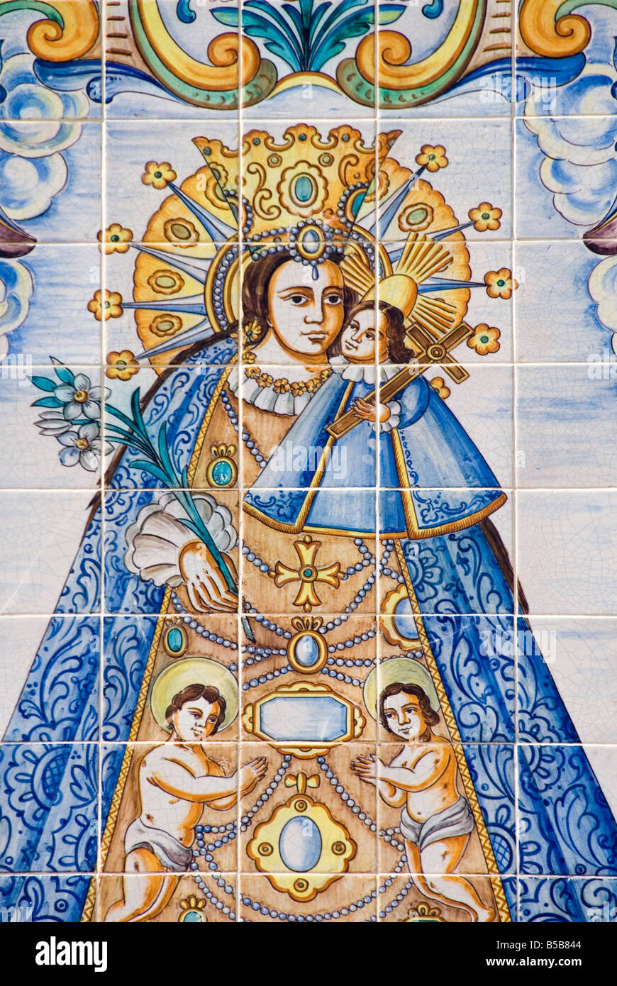 Hand painted glazed Azulejo tiles depicting the sacred statue and Patron Saint of the city of Valencia - Stock Image