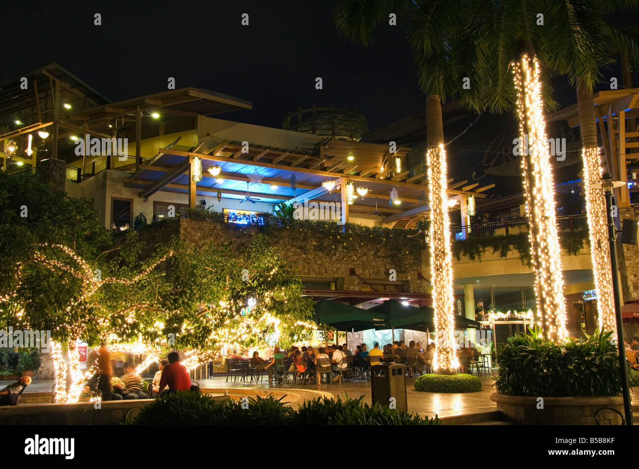 Greenbelt Entertainment Area with illuminated palm trees and outdoor dining, Makati District, Manila, Philippines, - Stock Image