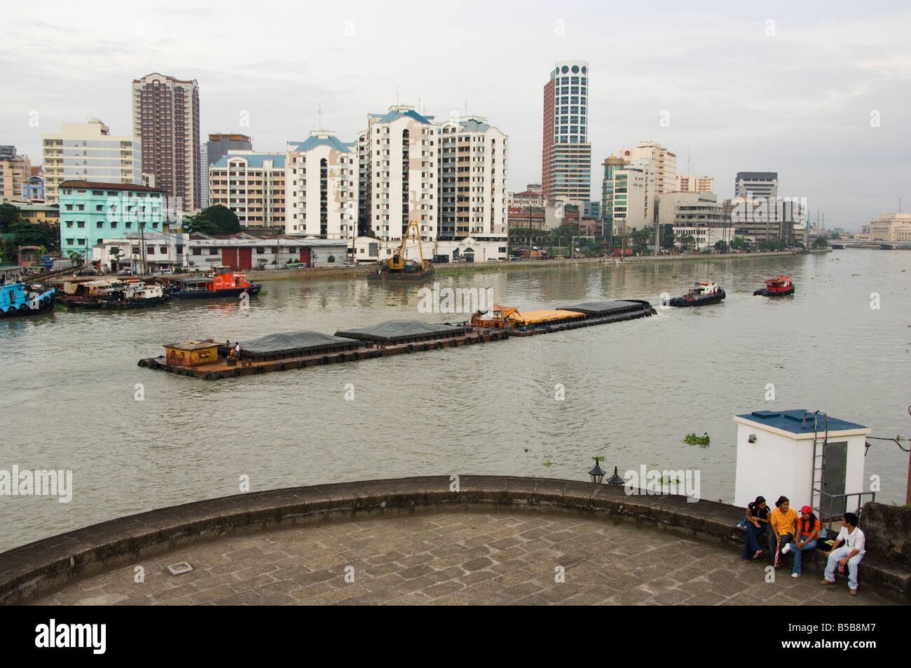 Barge on River Pasig with city skyline behind, Manila, Philippines, Southeast Asia - Stock Image