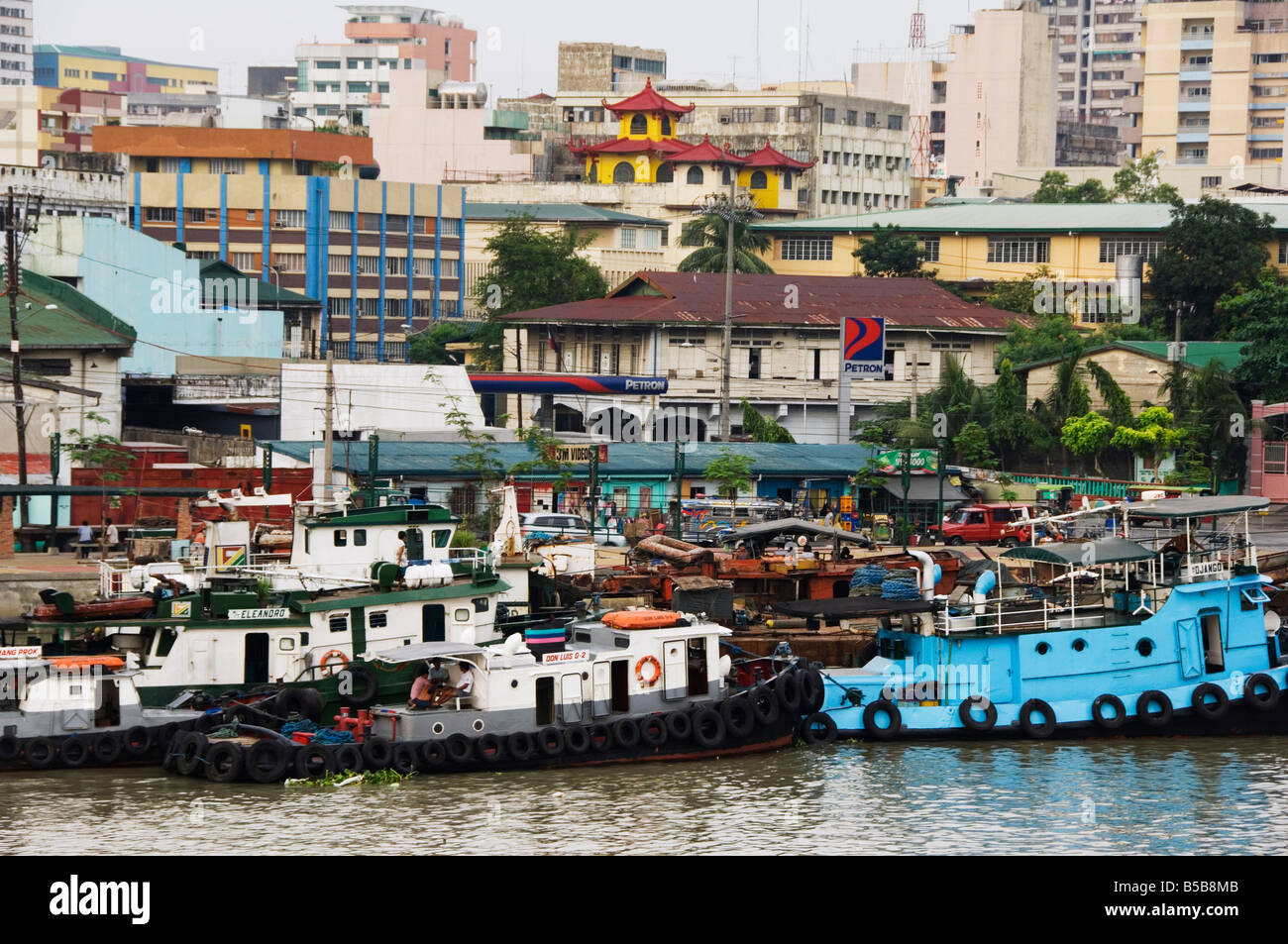 Barges on River Pasig with city buildings behind, Manila, Philippines, Southeast Asia - Stock Image