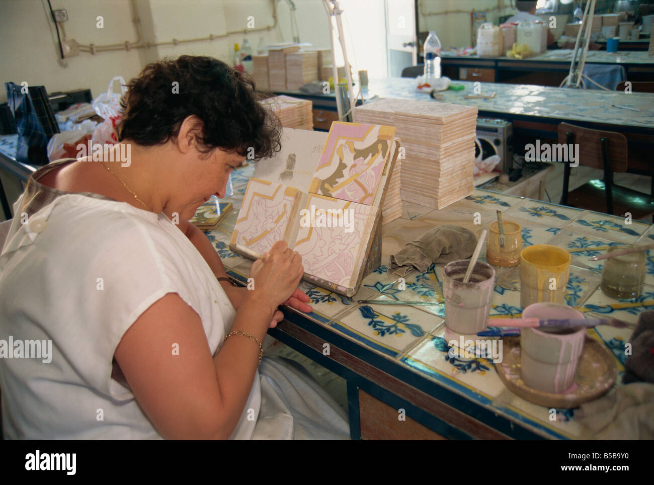 Woman painting on tiles, Sant'Ana azulejos factory, Lisbon, Portugal, Europe - Stock Image