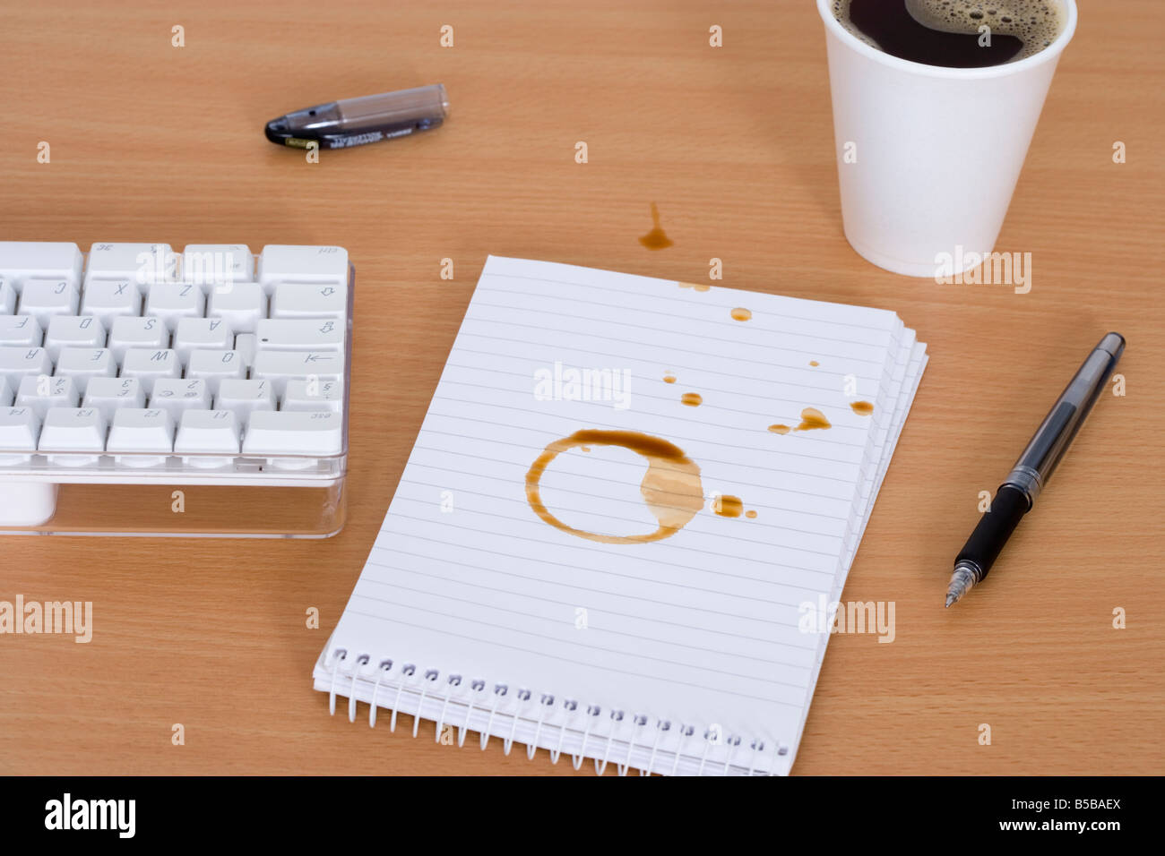 Spilt coffee over notebook on desk - Stock Image