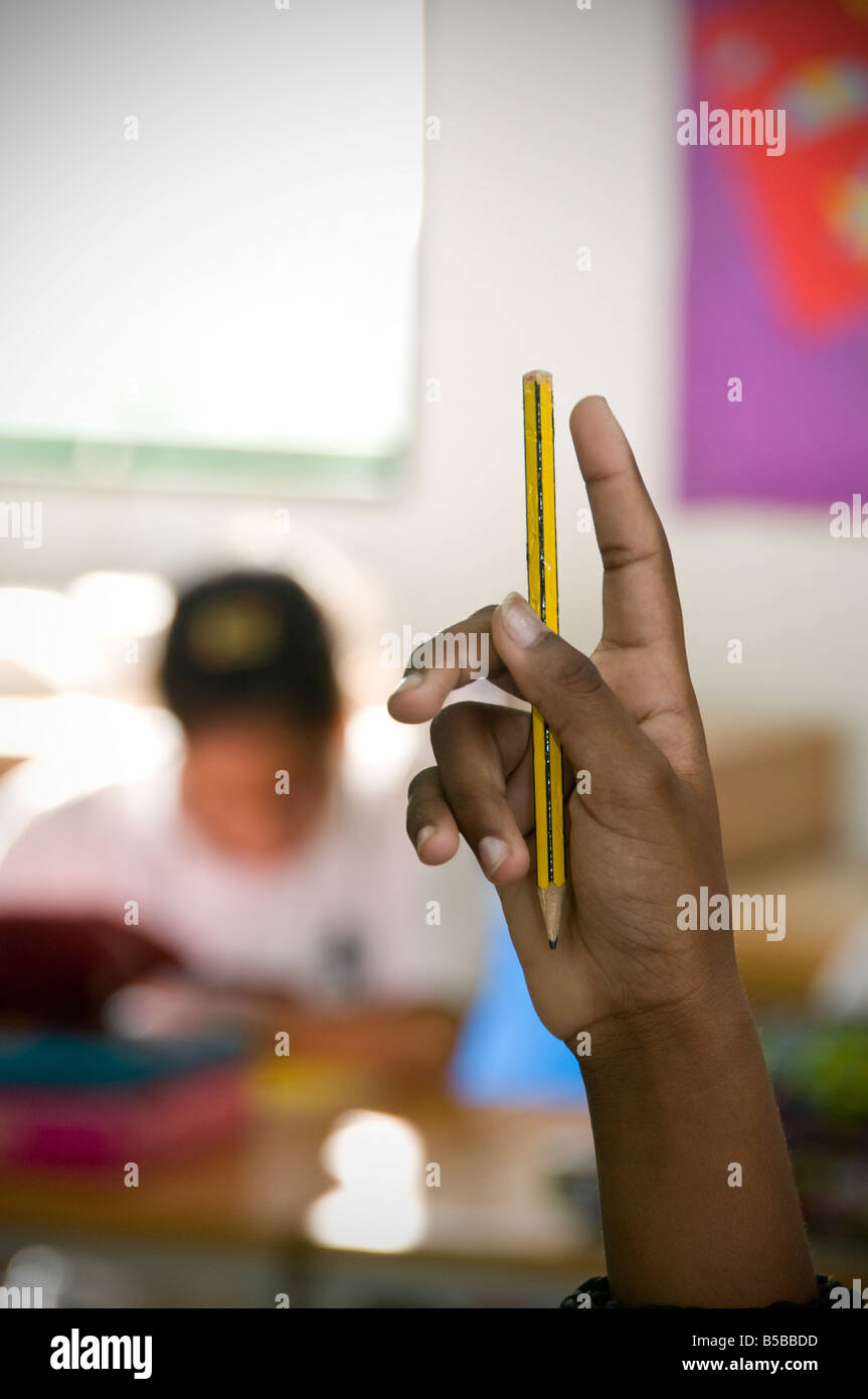 Dark skinned hand held up in classroom to answer question - Stock Image