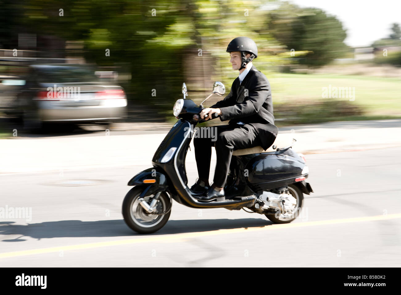 30 year old Caucasian male wearing a business suit riding a scooter downtown Montreal - Stock Image