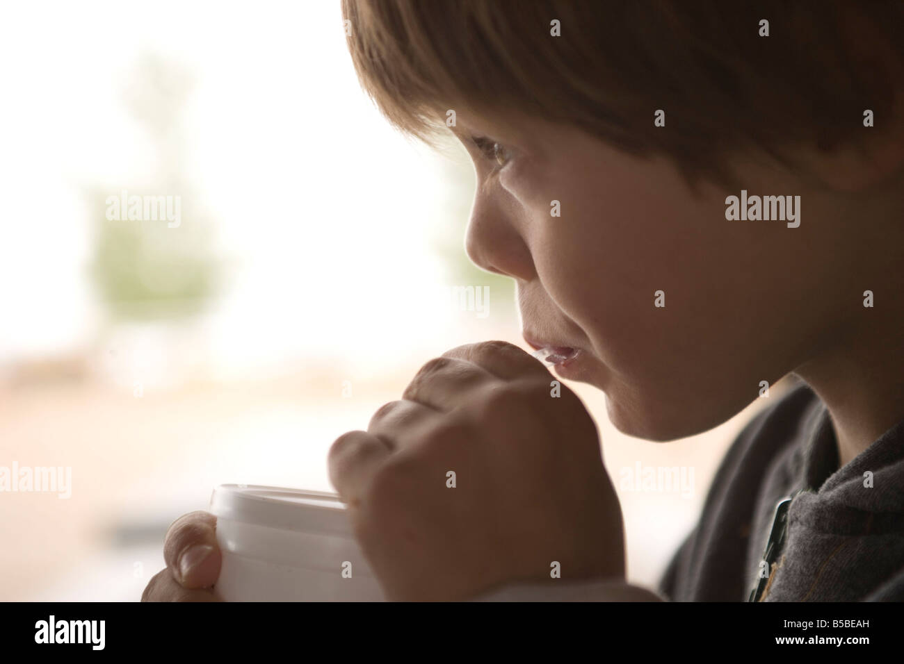 six year old boy drinking out of a straw - Stock Image