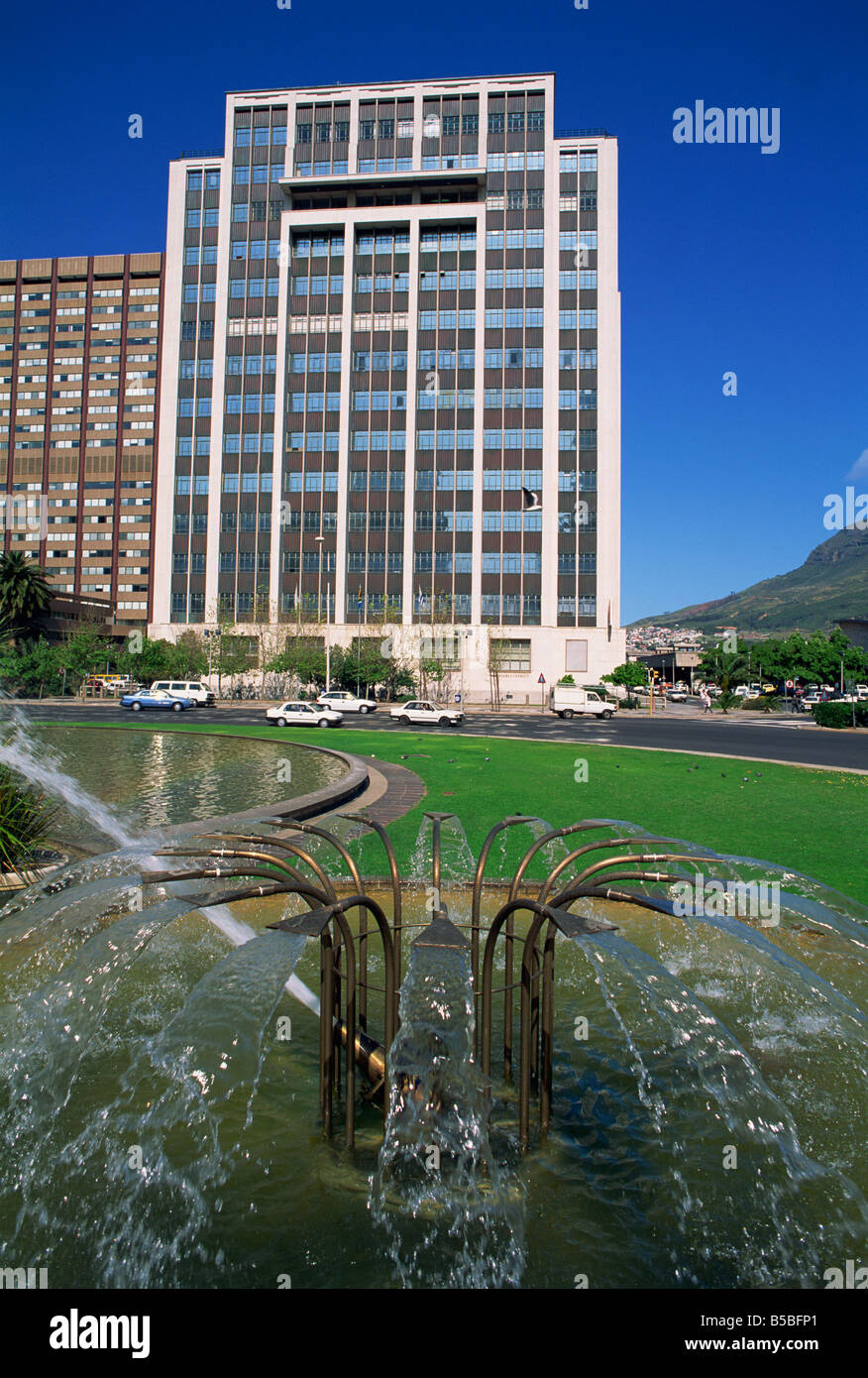 Water fountain in round a bout with an office building behind Central Business District Cape Town Cape Province - Stock Image