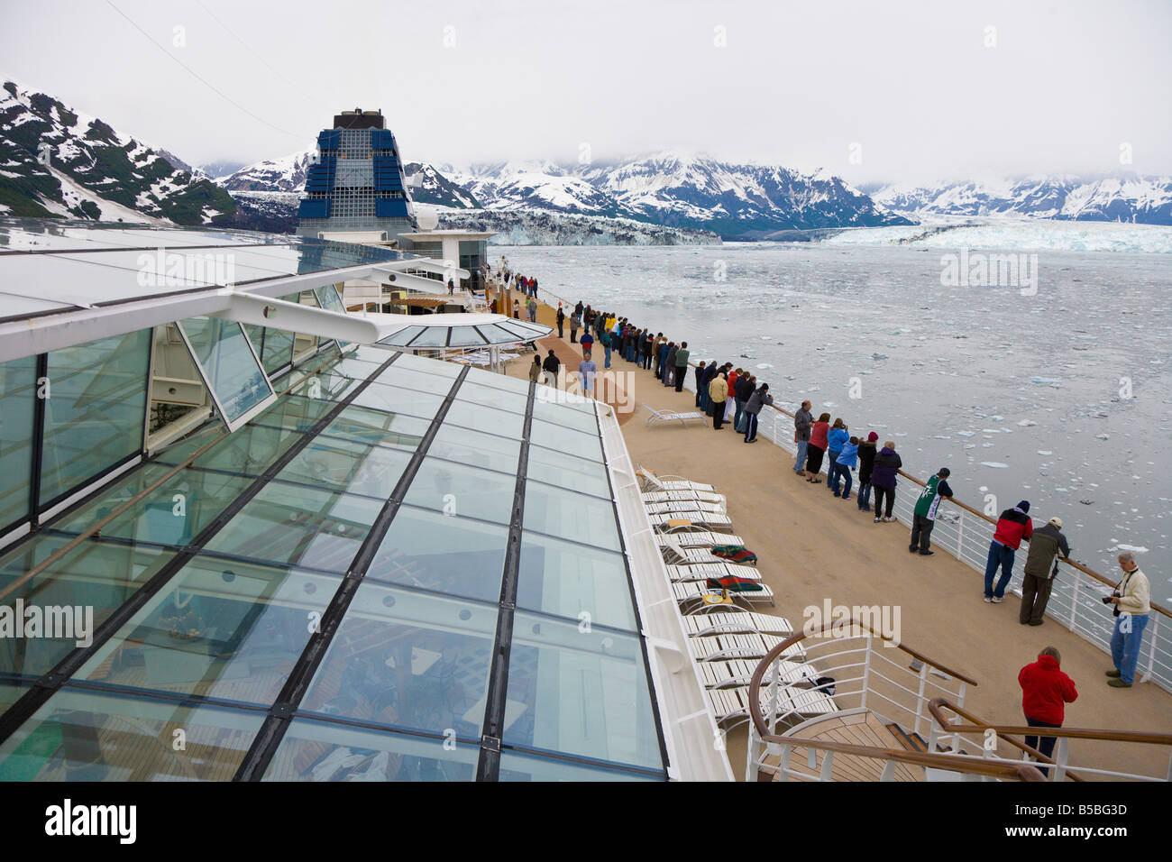 Cruise ship passengers line deck railing to see Hubbard Glacier in Disenchantment Bay and Yakutat Bay in Alaska - Stock Image