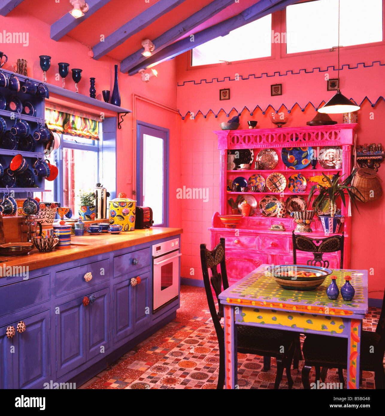 Brightly painted multicoloured table in bright pink kitchen ...