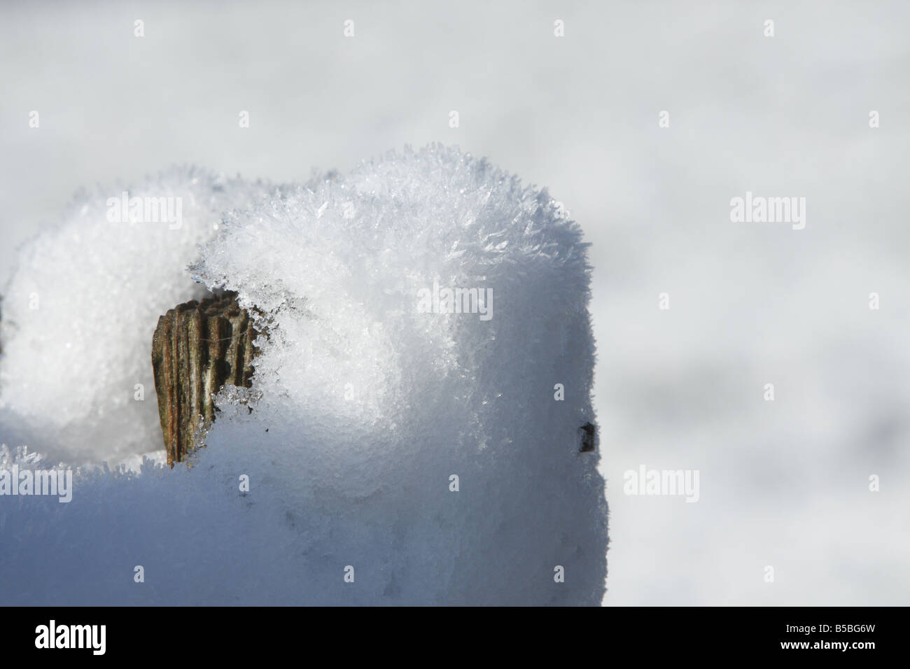 Fence post covered in snow - Stock Image