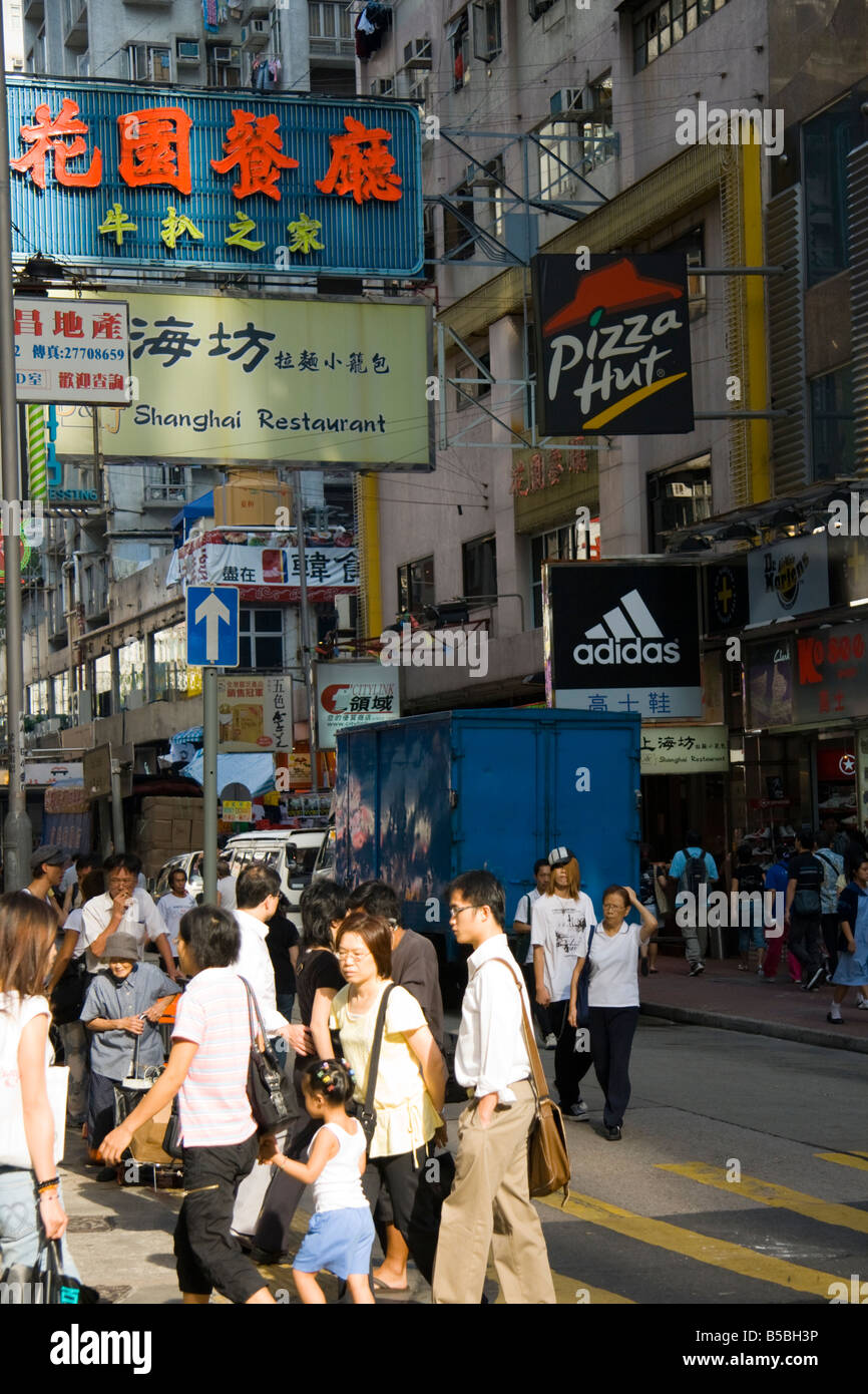 Shoppers in a street in Hong Kong advertising adidas and pizza hut - Stock Image