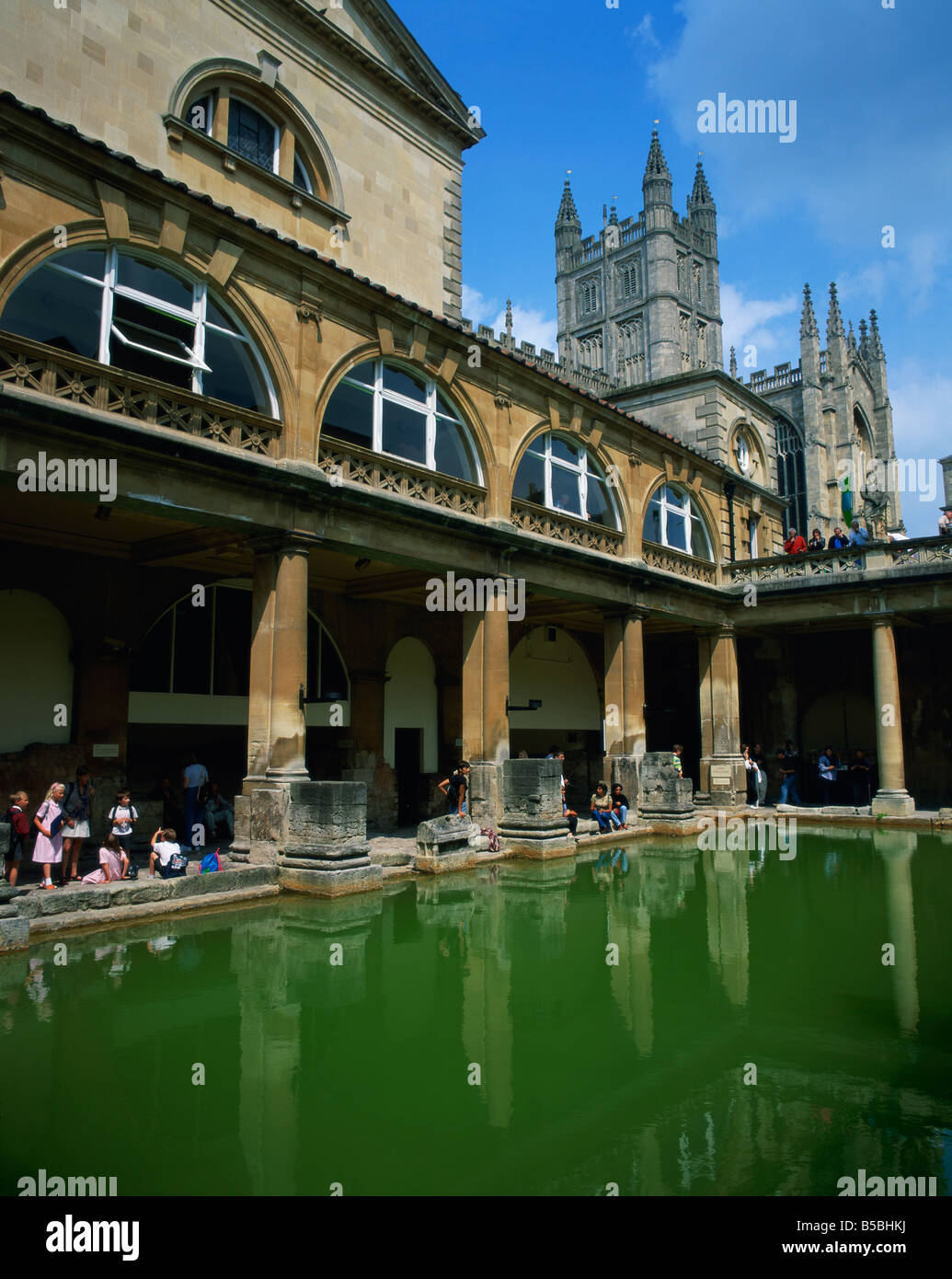 Visitors in the Roman Baths with the Abbey beyond in Bath UNESCO World Heritage Site Avon England United Kingdom - Stock Image