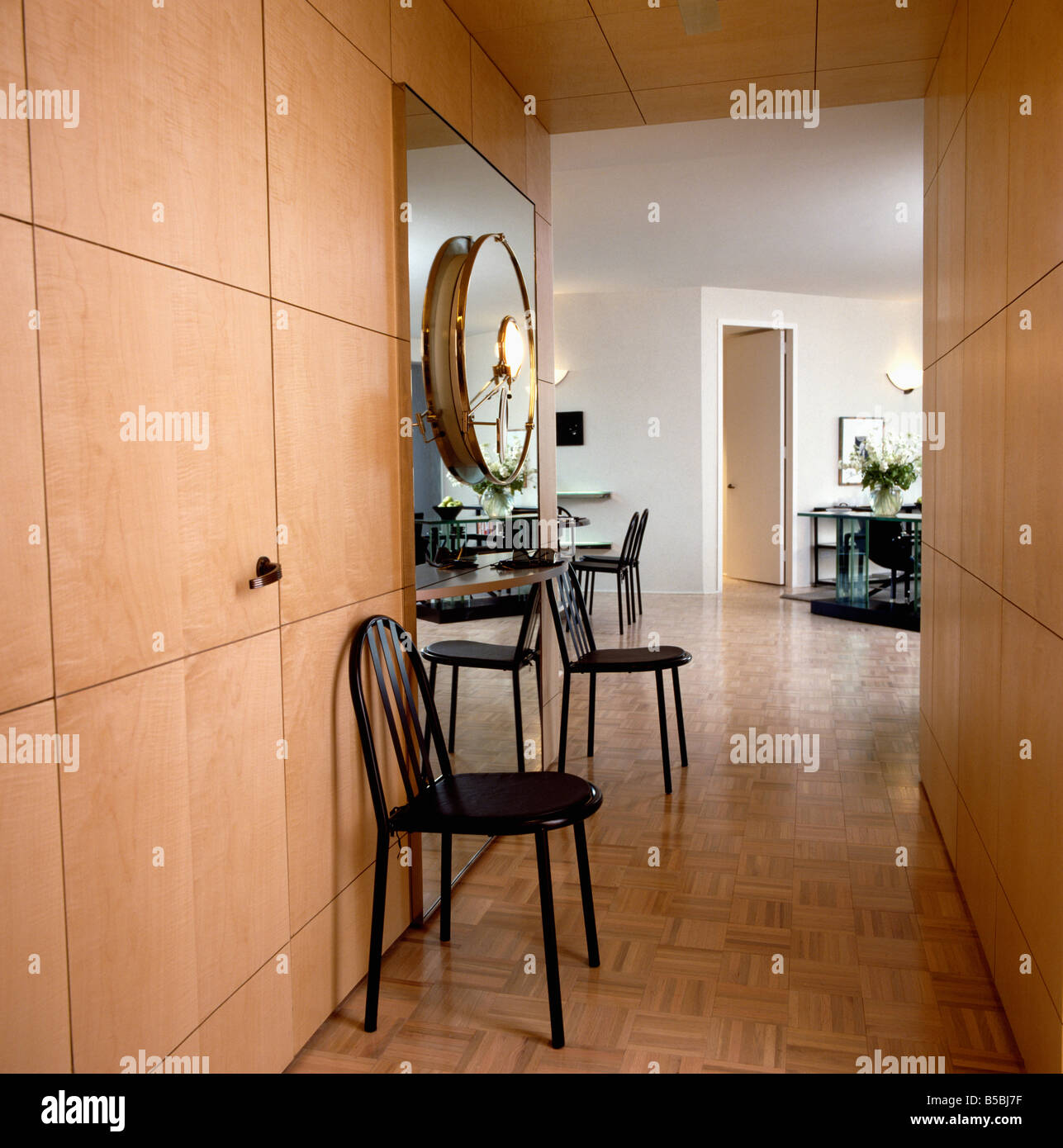 Black Metal Chairs Against Fitted Pale Wood Storage Cupboard In Modern  Openplan Apartment Hall With Clock And Woodblock Flooring