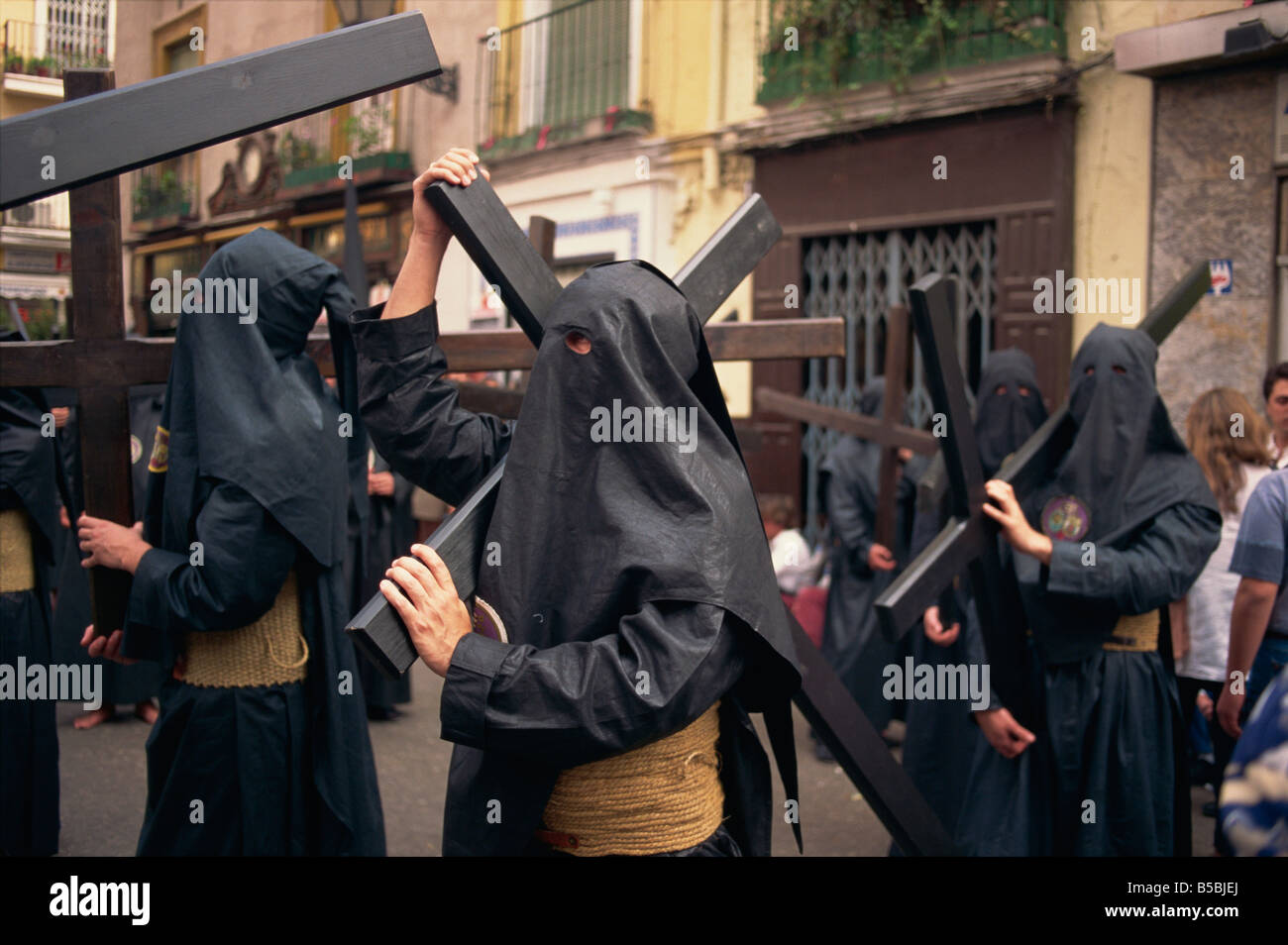 Penitents bearing crosses in procession Holy Week Semana Santa Seville Andalucia Sapin Europe - Stock Image