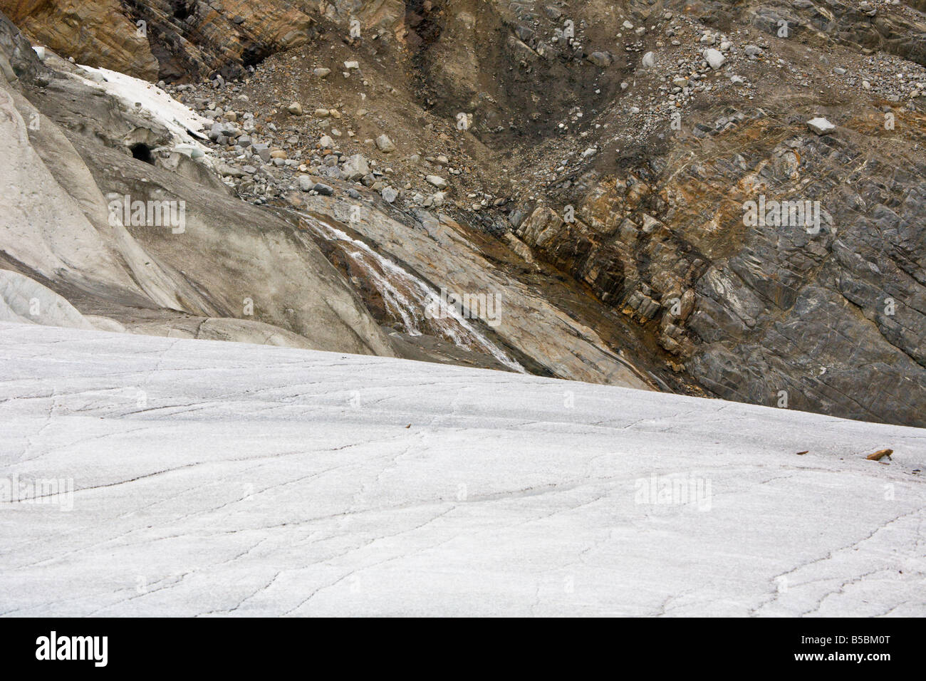 Rough mountain surface contrasts with smooth ice surface of Mendenhall Glacier near Juneau, Alaska - Stock Image