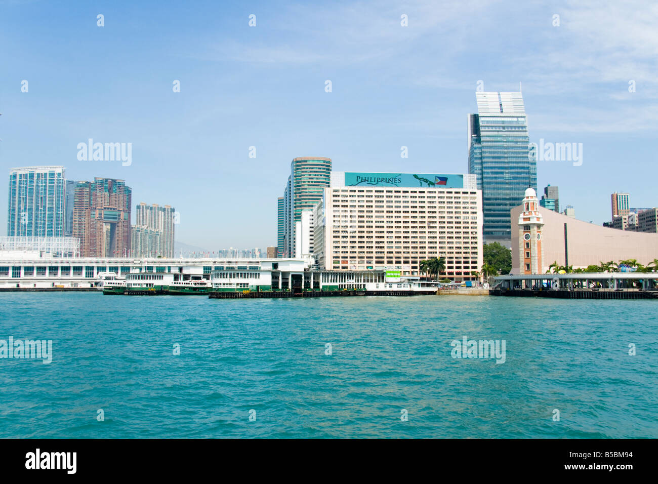 Star Ferry terminal with the clock tower , Victoria harbour, Kowloon, Hong Kong - Stock Image