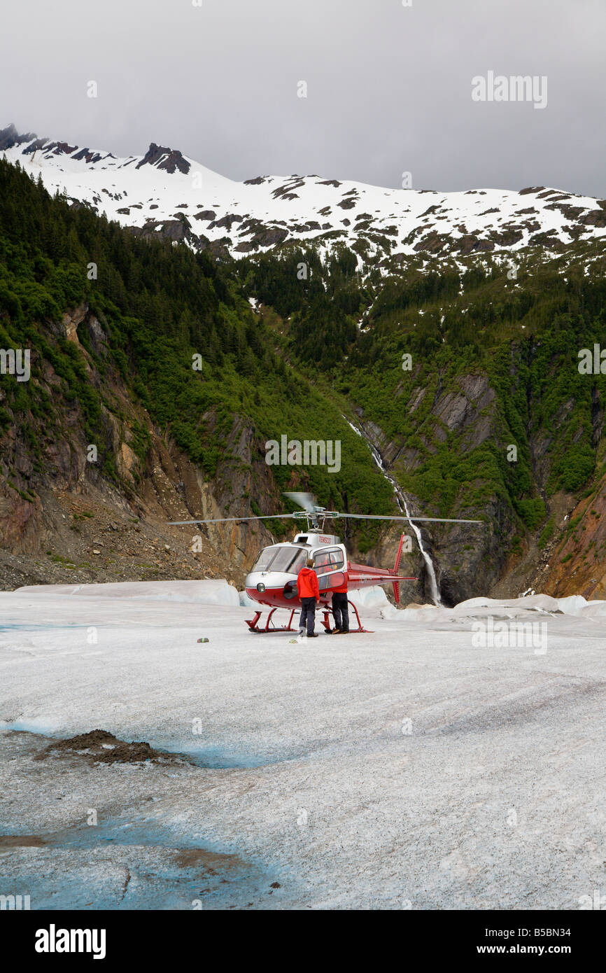 Helicoptor pilot and crew assist tourists in getting out of helicopter on top of Mendenhall Glacier near Juneau - Stock Image