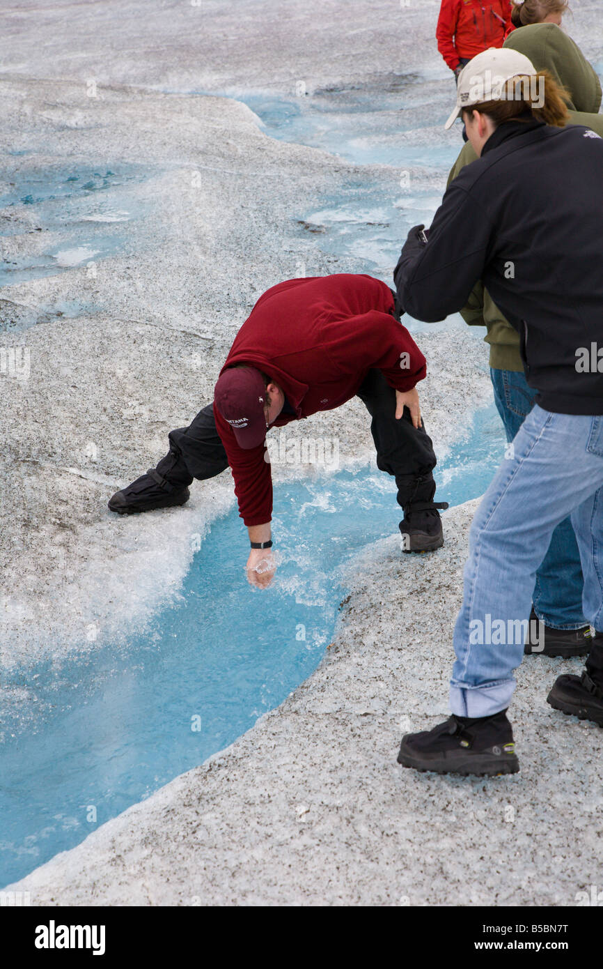 Tourist dips hand into glacier stream to drink the water of Mendenhall Glacier near Juneau Alaska - Stock Image