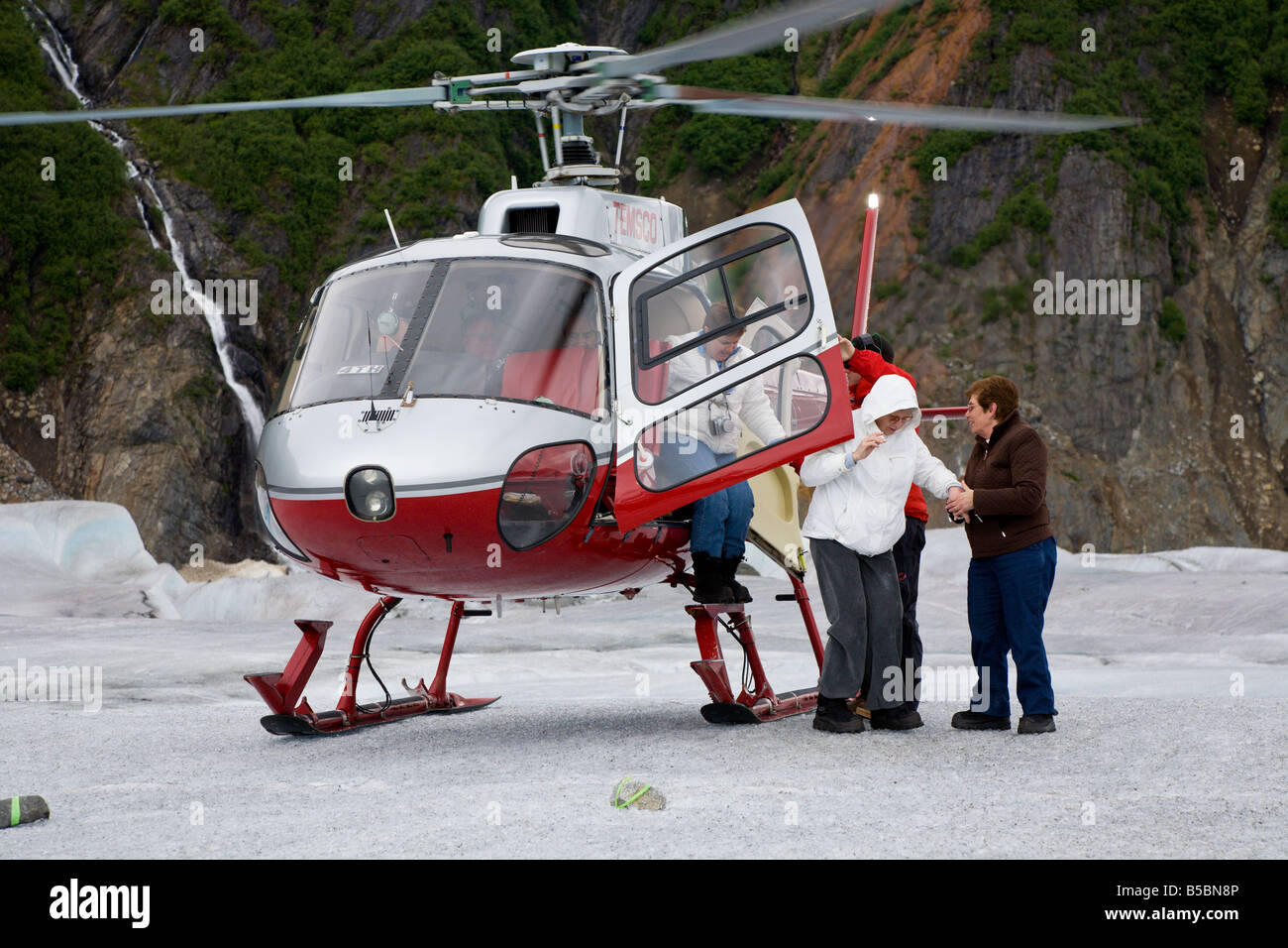 Helicoptor pilot and crew assist tourists getting out of tour helicopter on top of Mendenhall Glacier near Juneau - Stock Image