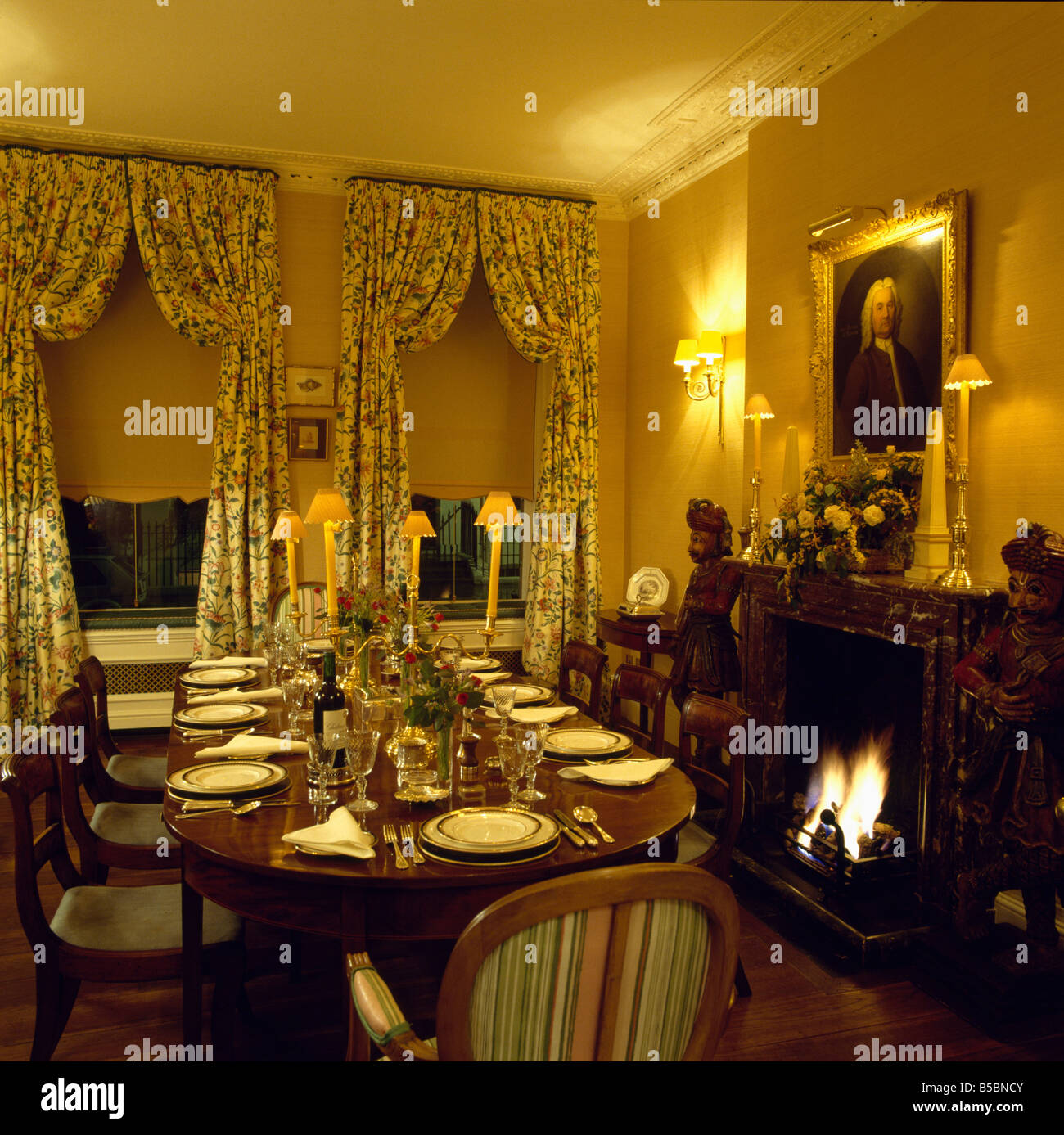 Antique Table In Yellow Dining Room With Blind And Floral Curtains On  Windows And Lighted Lamps Above Fireplace With Fire Lit