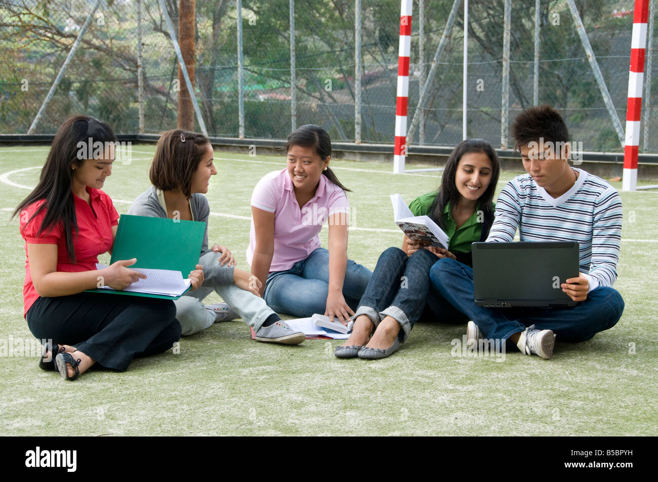 Group of senior teenage school students relax and talk together in an informal study break outside on school campus - Stock Image