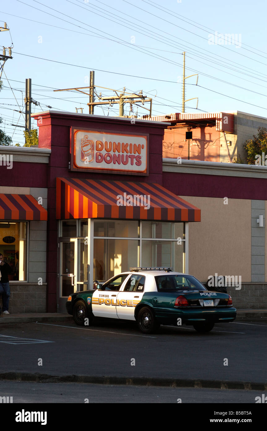 A Police car parked outside a Dunkin' Donuts store in Stamford Connecticut USA - Stock Image
