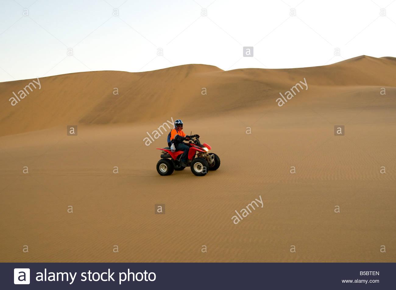 Riding Quad Bikes All Terrain Cycle in the Swakopmund Dunes Swakopmund Namib Desert Namibia - Stock Image