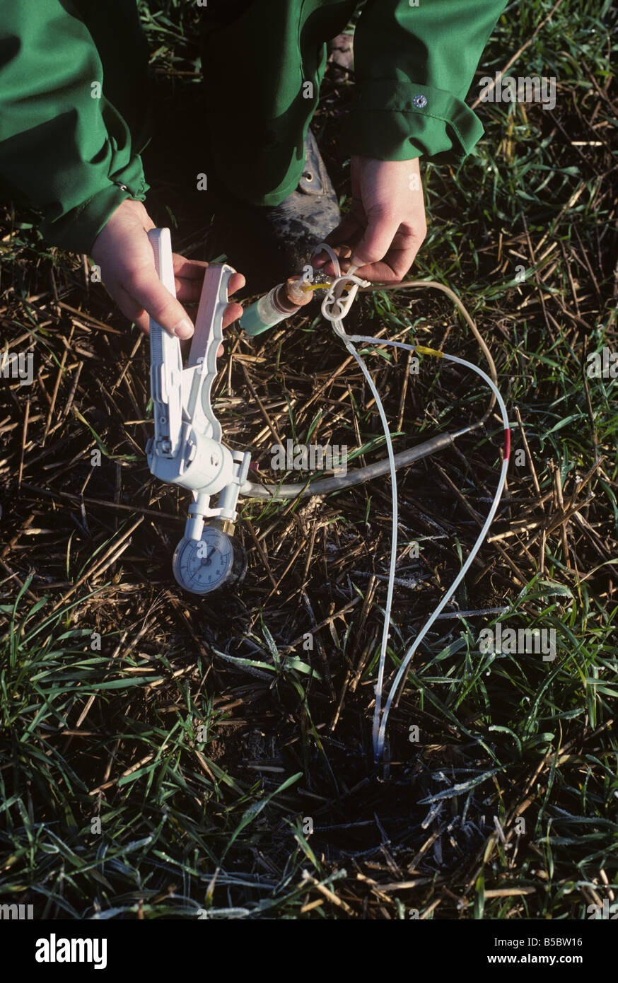 Technician drawing out lechate from porous pot placed in a bore hole - Stock Image
