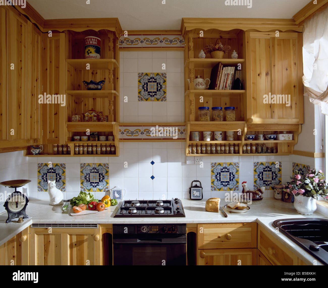 Superbe Pine Wall Units And White Tiled Wall With Decorative Spanish Tile Inserts  Above Worktop With Fitted Hob In Small Kitchen