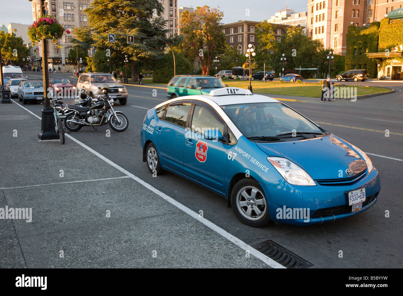 Blue Toyota Prius taxi parked at curb across from the