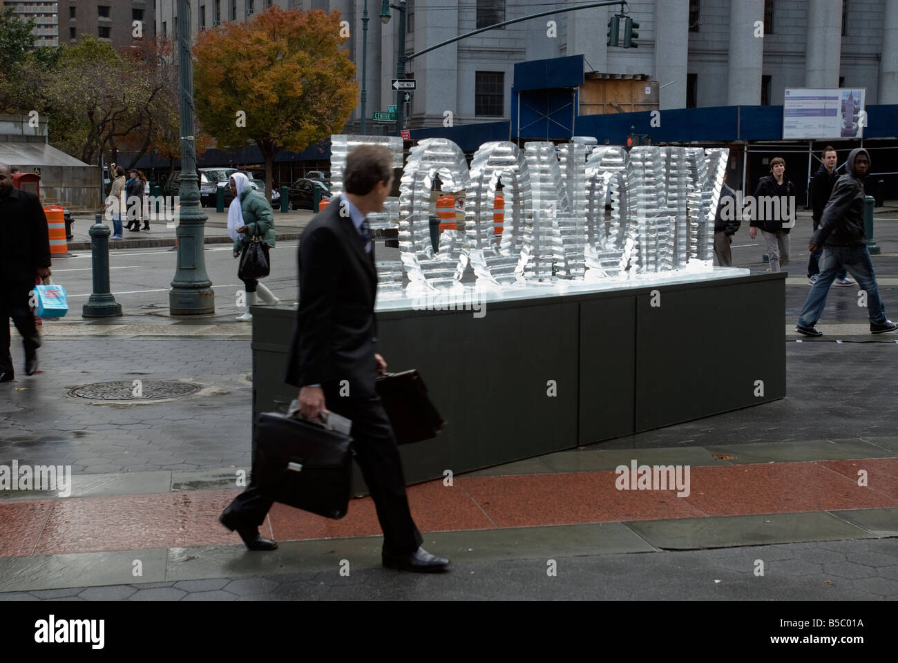 An ice sculpture of the word economy entitled Main Street Meltdown melts in Foley Square in New York - Stock Image