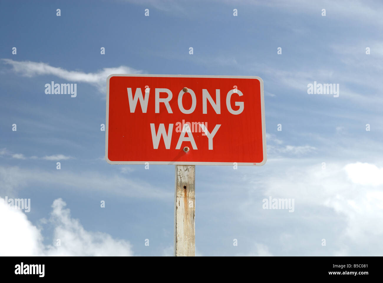 Wrong Way sign against blue sky - Stock Image