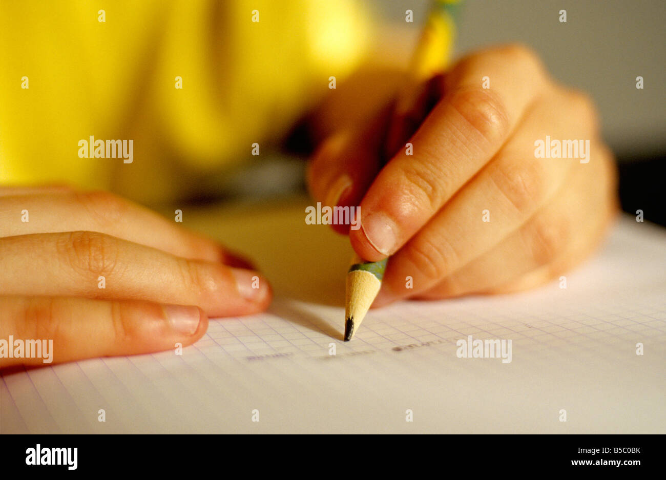 Hands of young left handed child doing homework - Stock Image