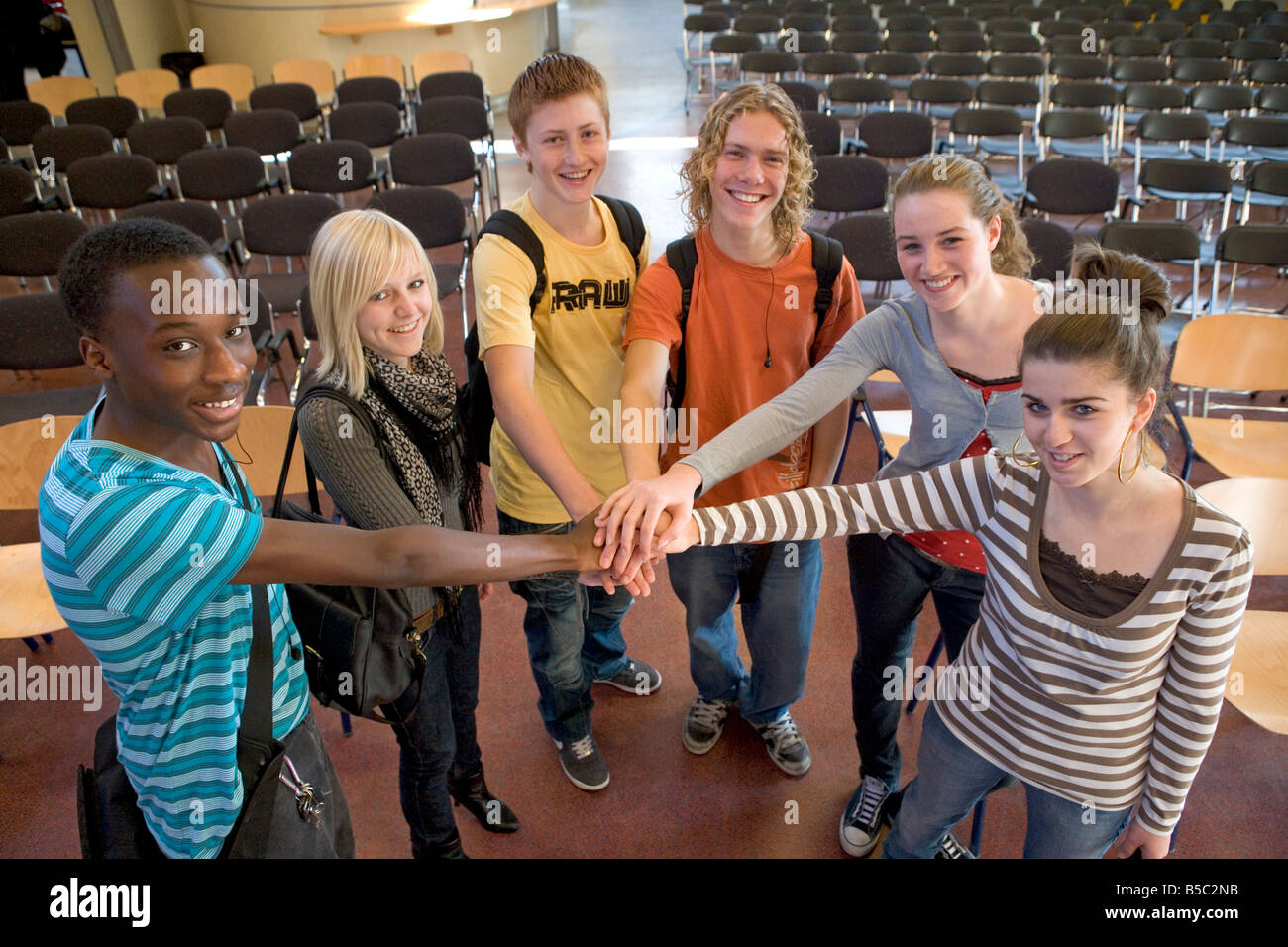 Group portrait of teenage boys and girls in the school hall - Stock Image