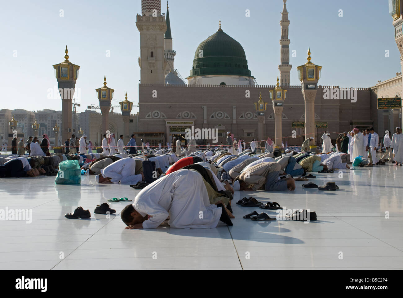 Pilgrims praying in congregation in front of the green dome of Masjid al Nabawi in Madinah Saudi Arabia - Stock Image