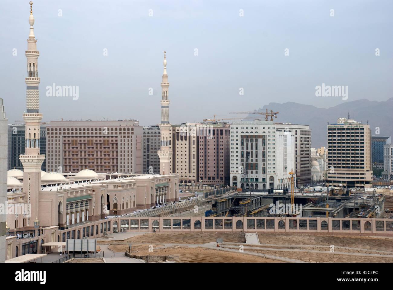 Jannat ul Baqi graveyard in the foreground Masjid al Nabawi and two of its minarets to the left Madinah Saudi Arabia - Stock Image