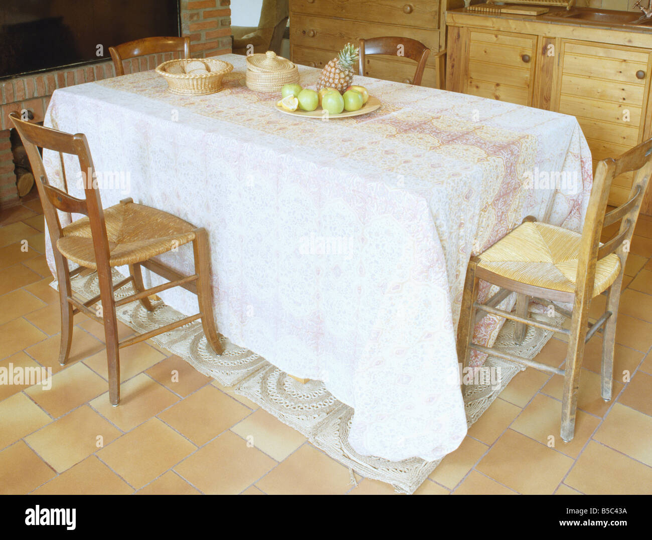 Rush-seated wooden chairs and rectangular table with long white ...