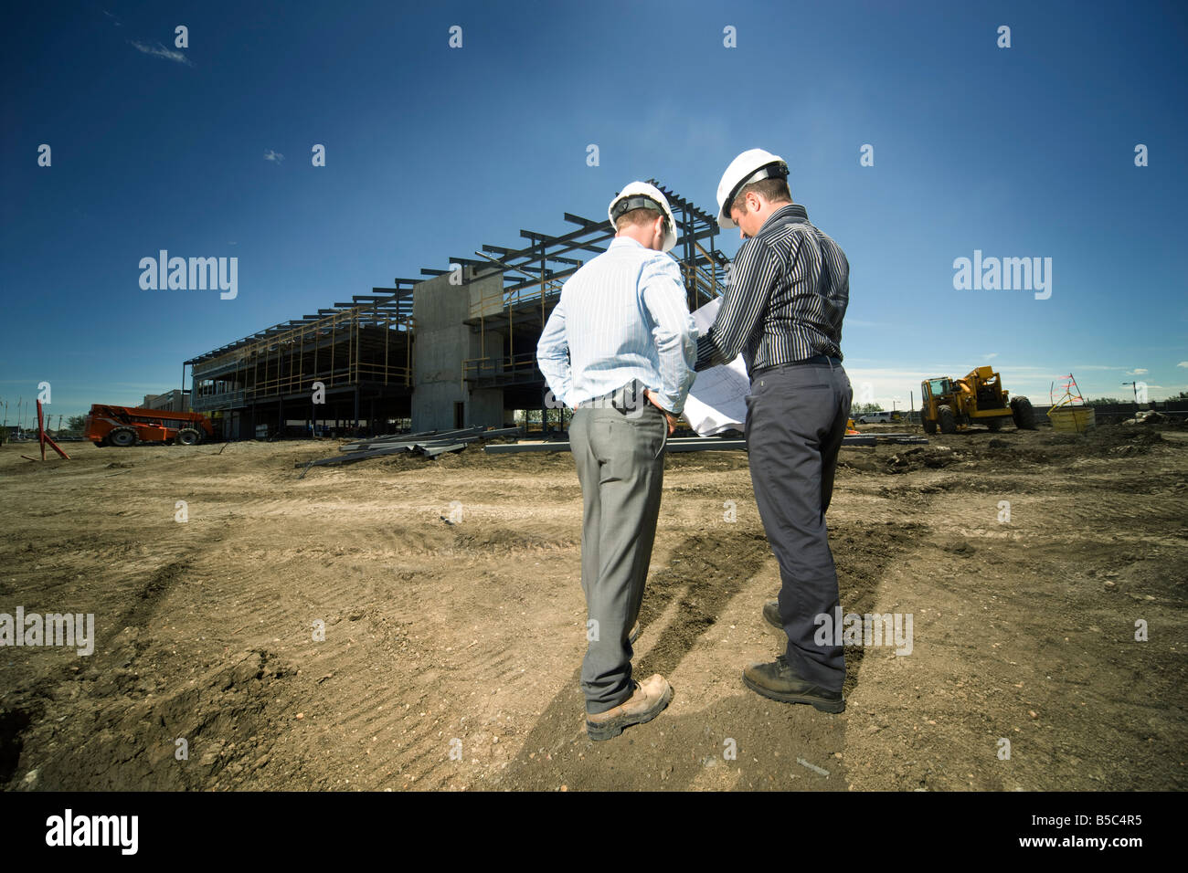 Two men reviewing blueprints in front of building - Stock Image