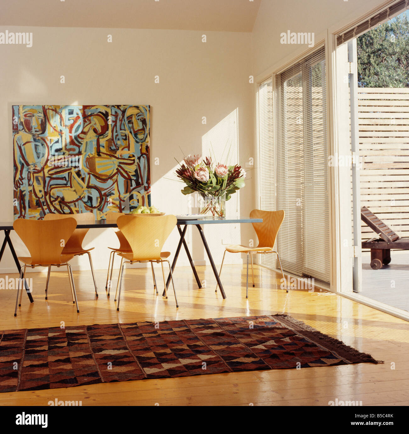 large abstract painting on wall of modern white dining room with arne jacobsen antchairs and rug on wooden flooring - Living Room Table Sets Painting