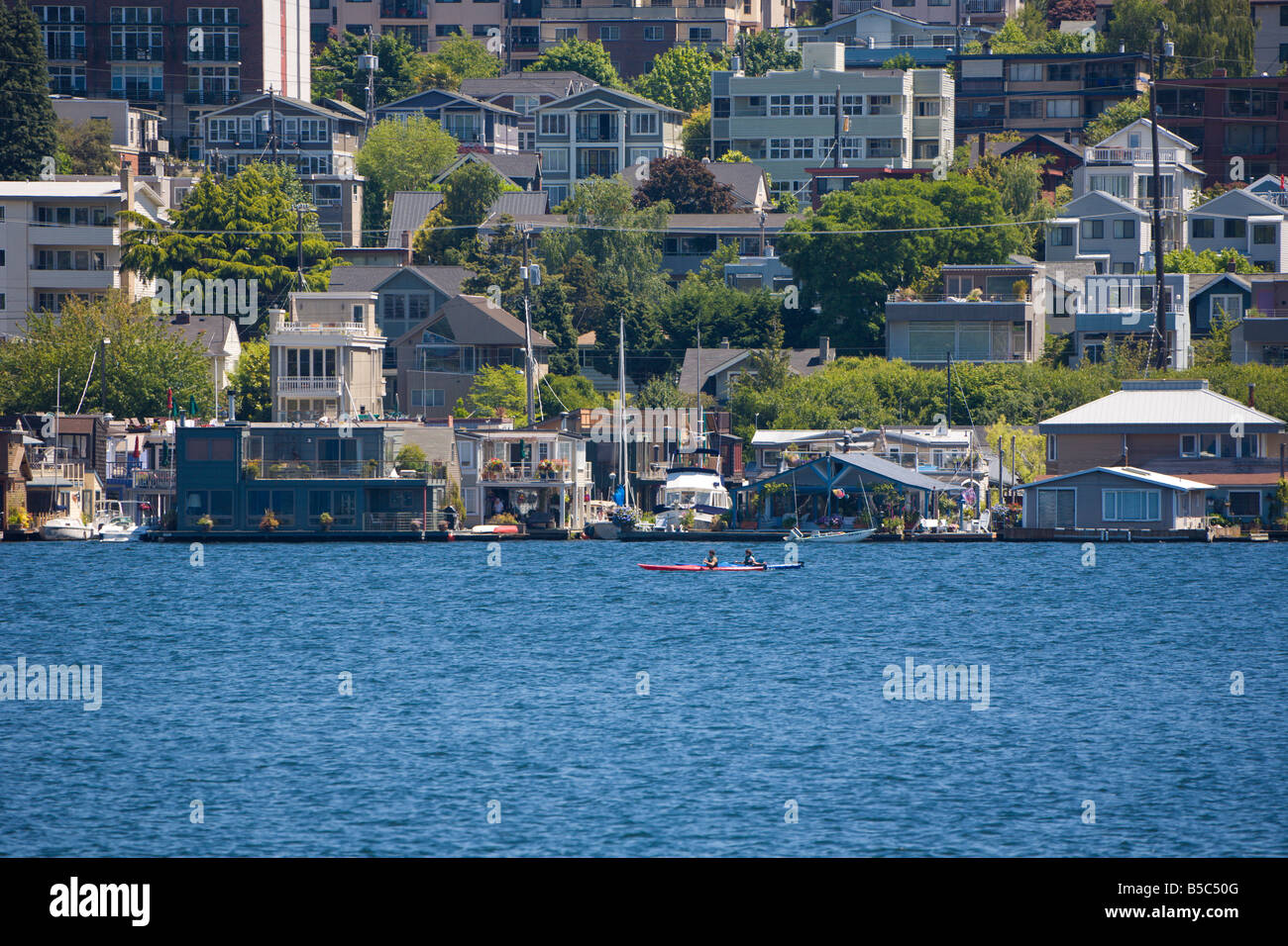 Two kayakers paddle past floating homes in the Eastlake neighborhood on Lake Union in Seattle, Washington - Stock Image
