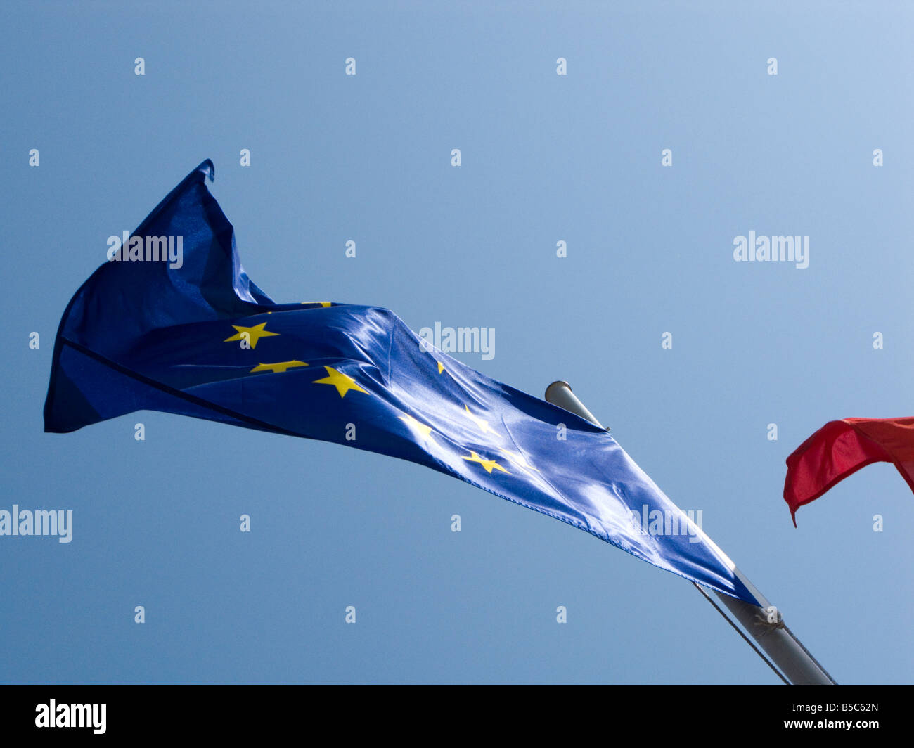 European Union flag flying against a clear blue sky - Stock Image