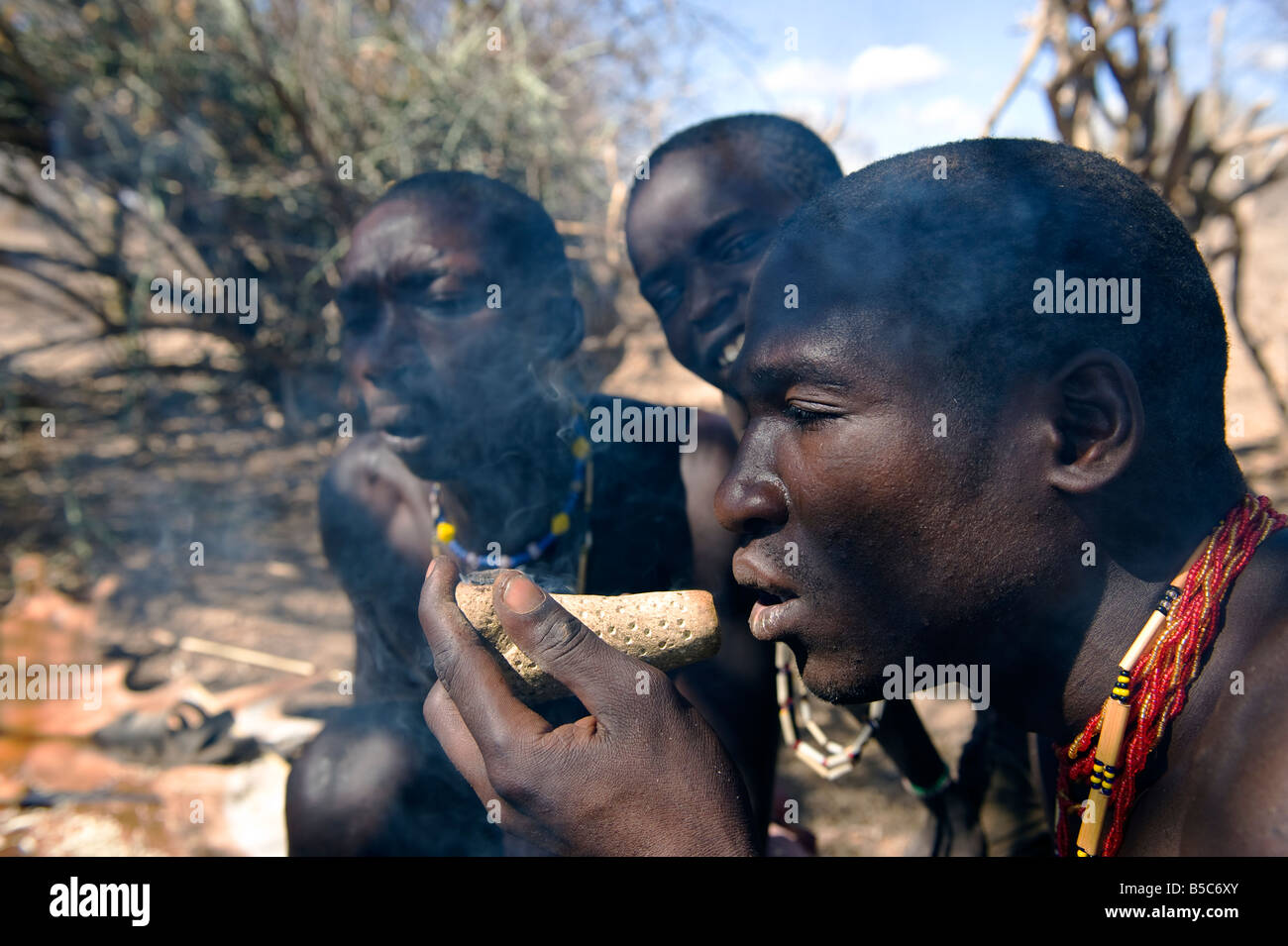 A man of the Hadza tribe smoking a pipe with marijuana Lake Eyasi Tanzania - Stock Image