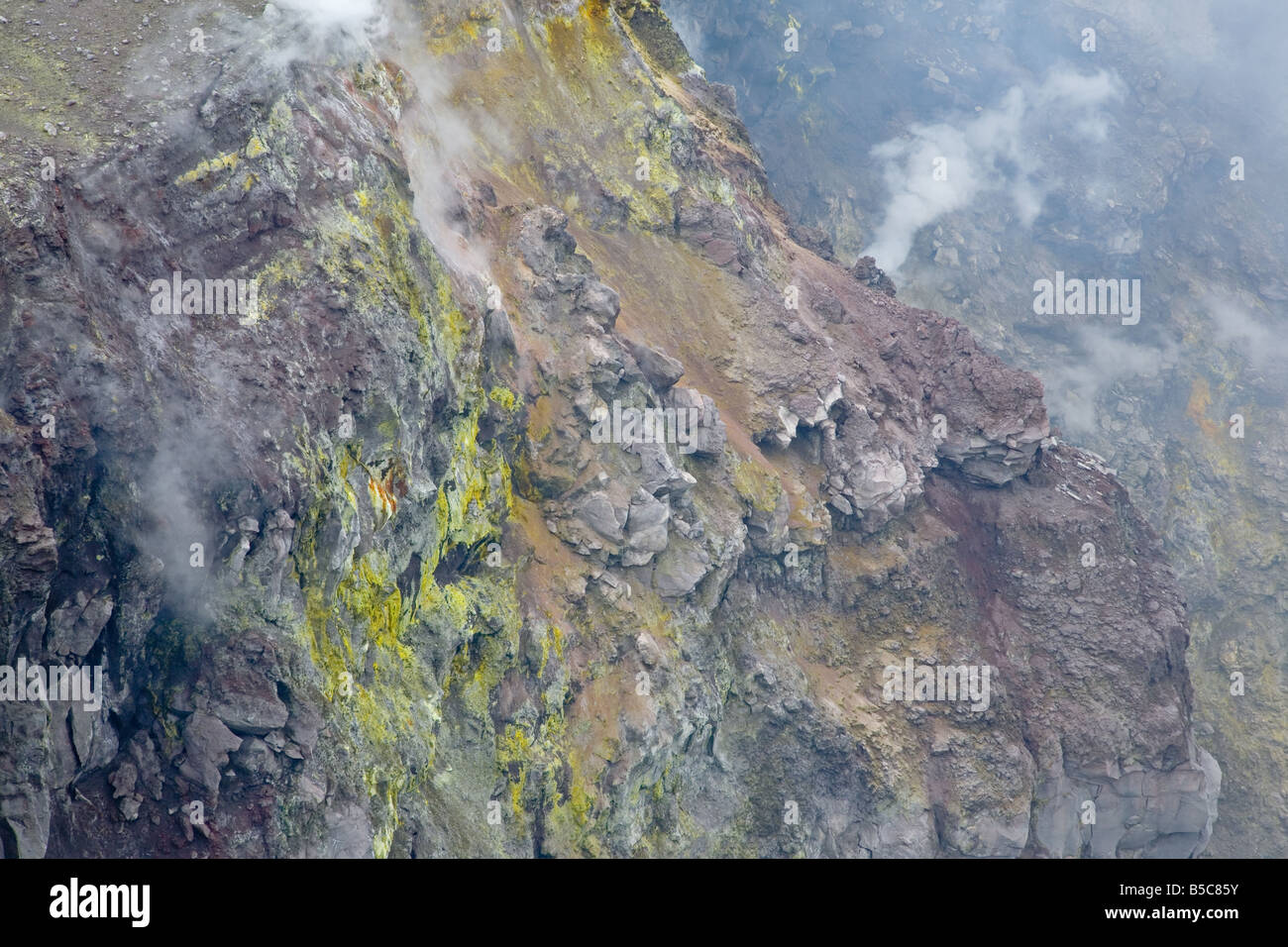 Sulphur and oxides from fumaroles at the inner crater rim of Mt Etna volcano - Stock Image