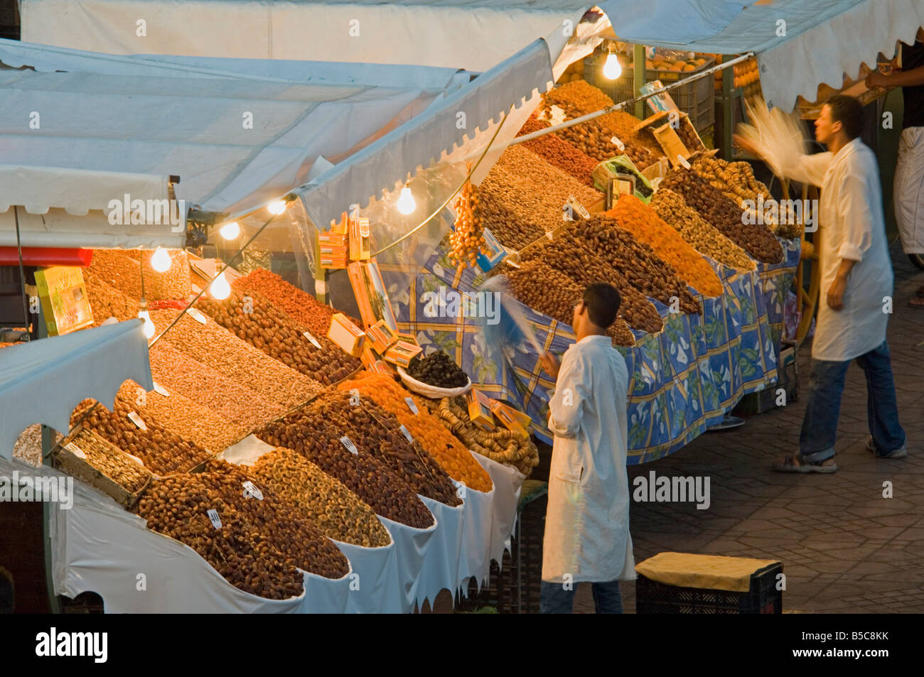 2 men prepare and clean their stalls selling dried food at the Djemaa El Fna in Marrakesh. Stock Photo