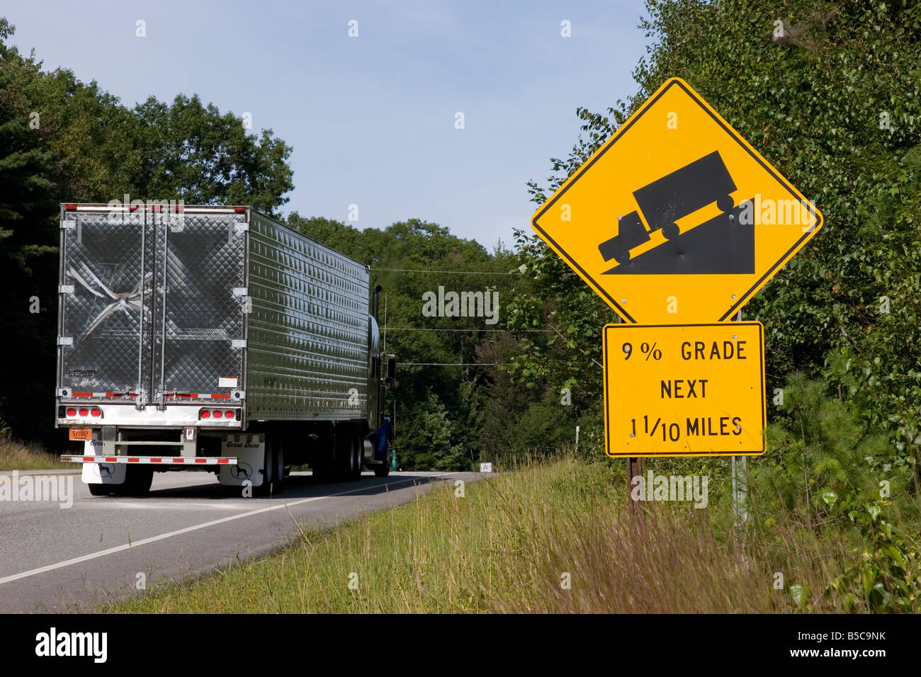 Semi truck drives past a road sign warning drivers of steep hill 9% grade ahead - Stock Image