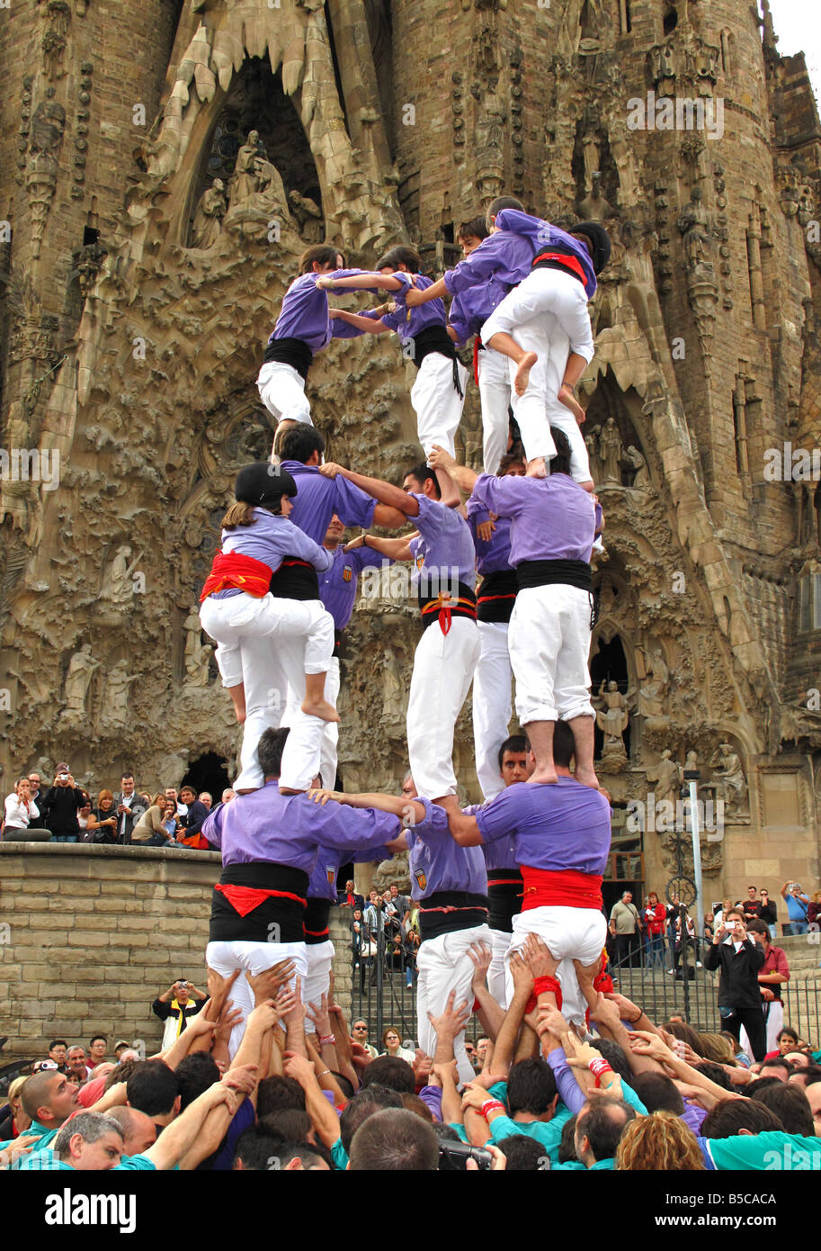 Castellers building human tower(castell) outside Gaudi's La Sagrada Familia Cathedral, Barcelona, Spain - Stock Image
